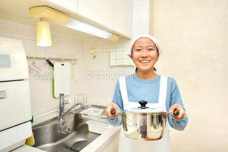 キッチンで笑う女の子の写真素材 [FYI03452311]