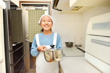 キッチンで笑う女の子の写真素材 [FYI03452399]