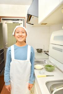 キッチンで料理をする女の子の写真素材 [FYI03452511]