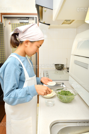 キッチンで料理をする女の子の写真素材 [FYI03452512]
