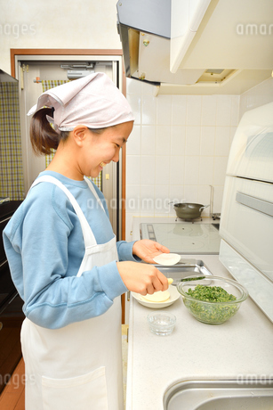キッチンで料理をする女の子の写真素材 [FYI03452513]