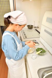 キッチンで料理をする女の子の写真素材 [FYI03452656]