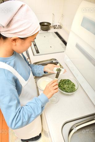 キッチンで料理をする女の子の写真素材 [FYI03452657]