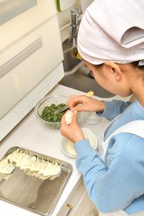 キッチンで料理をする女の子の写真素材 [FYI03452658]