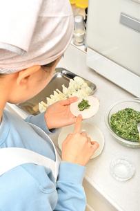 キッチンで料理をする女の子の写真素材 [FYI03452661]