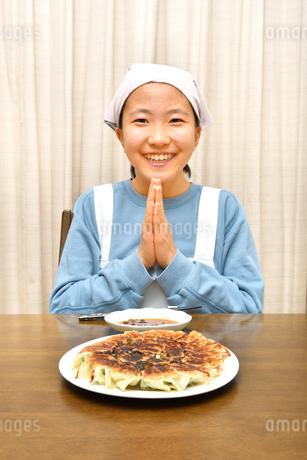 餃子を食べる女の子(合掌)の写真素材 [FYI03452842]