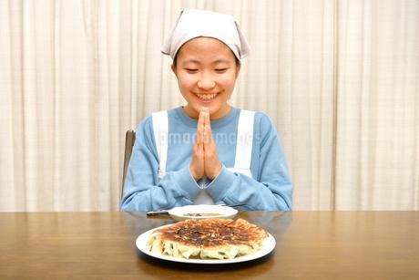 餃子を食べる女の子(合掌)の写真素材 [FYI03452843]
