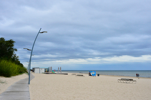 ラトビア・ユールマラのリガ湾のビーチに並ぶ街灯柱と散歩する人びとの写真素材 [FYI03453551]