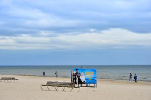 ラトビア・ユールマラのリガ湾のビーチを散歩する人と更衣する為のカラフルな広告の入った設置物の写真素材 [FYI03453552]