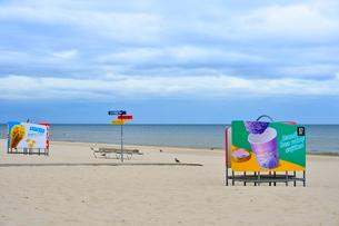 ラトビア・ユールマラのリガ湾のビーチの更衣する為のカラフルな広告の入った設置物と案内板の写真素材 [FYI03453554]