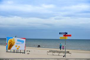 ラトビア・ユールマラのリガ湾のビーチを散歩する人と更衣する為のカラフルな広告の入った設置物と案内ボードの写真素材 [FYI03453557]