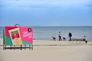 ラトビア・ユールマラのリガ湾のビーチを犬の散歩する人と更衣する為のカラフルな広告の入った設置物の写真素材 [FYI03453566]