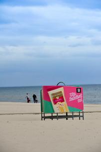 ラトビア・ユールマラのリガ湾のビーチを犬の散歩する人と更衣する為のカラフルな広告の入った設置物の写真素材 [FYI03453567]