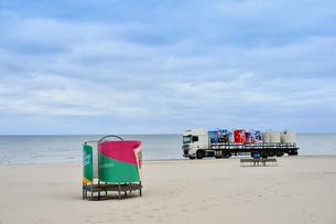 ラトビア・ユールマラのリガ湾のビーチを走るトラックと更衣する為のカラフルな広告の模様のついた設置物の写真素材 [FYI03453568]