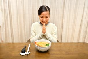 年越しそばを食べる女の子(大晦日、合掌)の写真素材 [FYI03454875]