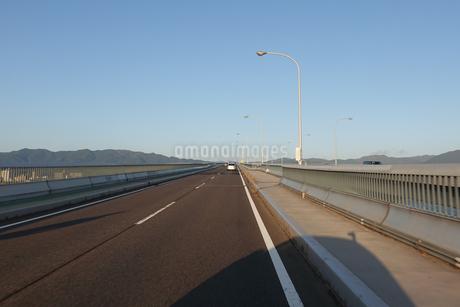 早朝の琵琶湖大橋をドライブの写真素材 [FYI03454919]