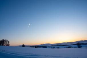 冬の夕暮れの空と飛行機雲の写真素材 [FYI03455027]