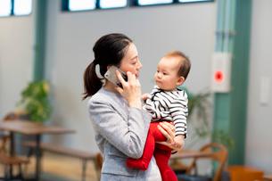 赤ちゃんを抱きかかえながら通話する女性の写真素材 [FYI03455532]