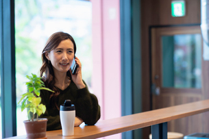 カフェで通話する女性の写真素材 [FYI03455539]