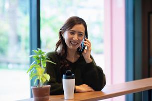 カフェで通話する女性の写真素材 [FYI03455541]