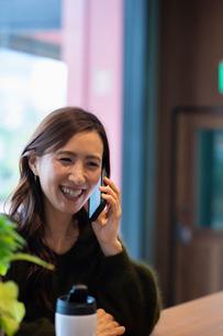 カフェで通話する女性の写真素材 [FYI03455544]