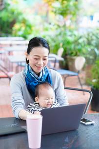 赤ちゃんをあやしながら作業する女性の写真素材 [FYI03455716]