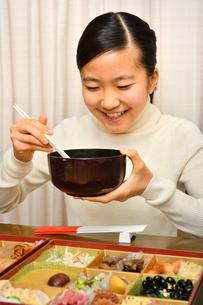 おせち料理を食べる女の子(正月)の写真素材 [FYI03455906]