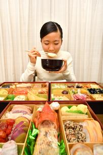 おせち料理を食べる女の子(正月)の写真素材 [FYI03455908]