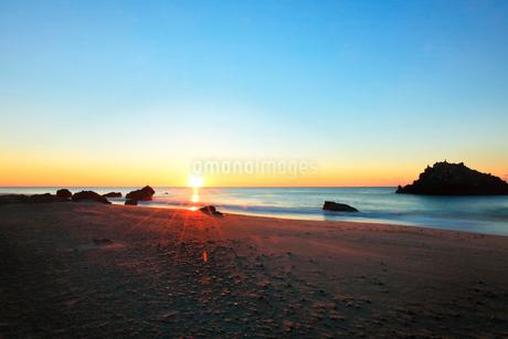浜辺に寄せる波と朝日の写真素材 [FYI03455918]