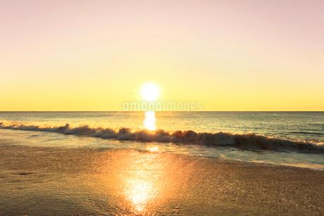 浜辺に寄せる波と朝日の写真素材 [FYI03455920]