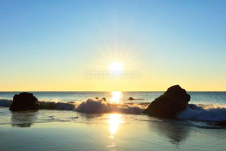 浜辺に寄せる波と朝日の写真素材 [FYI03455921]