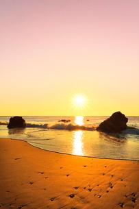 浜辺に寄せる波と朝日の写真素材 [FYI03455922]