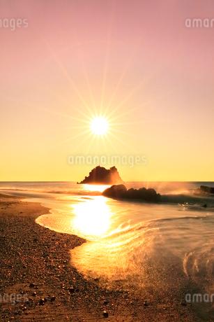 浜辺に寄せる波と朝日の写真素材 [FYI03455926]