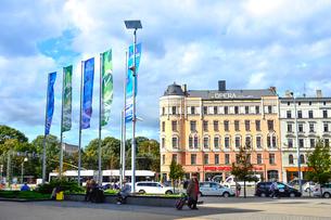 ラトビア・首都リガの中央駅前に並ぶ旗とホテルなどの建物と行き交う車の写真素材 [FYI03456537]