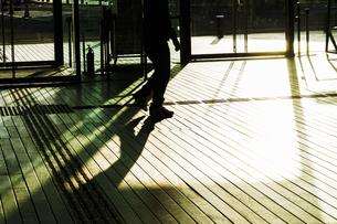 ウッドデッキを歩く人々の影の写真素材 [FYI03456621]