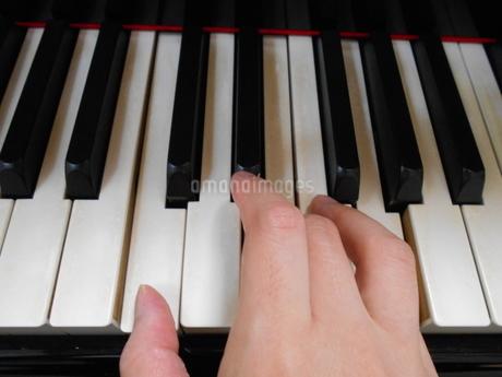 片手でピアノを弾くの写真素材 [FYI03457336]