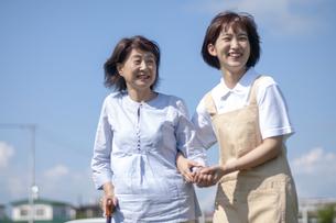介護士に歩行を介助してもらうシニア女性の写真素材 [FYI03457376]