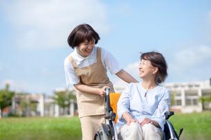 介護士と話をする車椅子のシニア女性の写真素材 [FYI03457383]