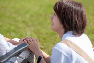 車椅子の女性の手を握る介護士の写真素材 [FYI03457386]
