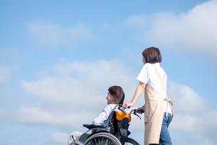 車椅子を押す介護士の女性の写真素材 [FYI03457389]