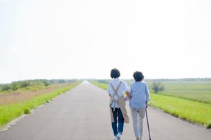 シニア女性の歩行を介助する介護士の後ろ姿の写真素材 [FYI03457390]
