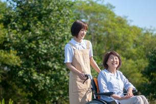 車椅子を押す介護士の女性の写真素材 [FYI03457396]
