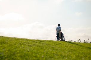 土手で車椅子を押す介護士の女性の写真素材 [FYI03457404]