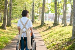 車椅子を押す介護士の女性の写真素材 [FYI03457408]