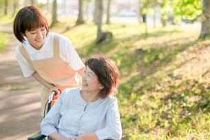 遊歩道で介護士と話をするシニア女性の写真素材 [FYI03457412]