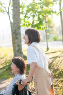 車椅子を押す介護士の女性の写真素材 [FYI03457417]