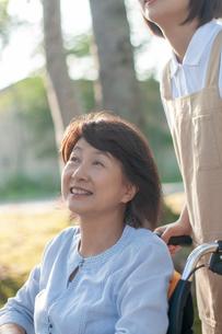 介護士の女性に車椅子を押してもらうシニア女性の写真素材 [FYI03457418]