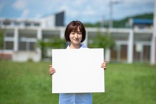 ホワイトボードを持つ介護士の女性の写真素材 [FYI03457420]