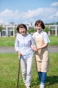 シニア女性の歩行を介助する介護士の写真素材 [FYI03457429]