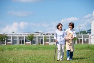 シニア女性の歩行を介助する介護士の写真素材 [FYI03457432]